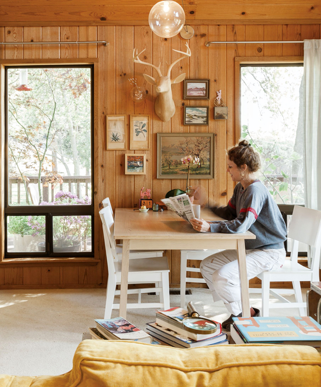 Artist Sarah Coleman relaxes at the dining table in the open living space. 'With design, I don't want to be limited by any one style,' she says.